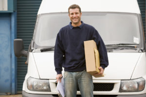 Deliveryperson standing with van holding clipboard and box smili